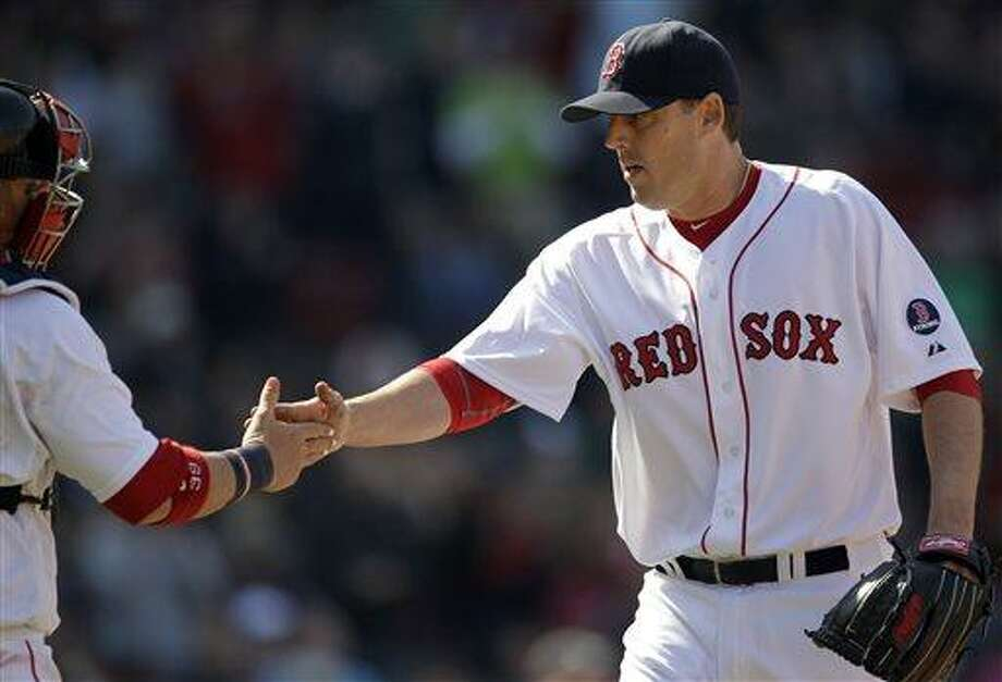 Boston Red Sox starting pitcher John Lackey, right, is congratulated by catcher Jarrod Saltalamacchia after the last out in the sixth inning of a baseball game against the Houston Astros at Fenway Park in Boston, Sunday, April 28, 2013. (AP Photo/Mary Schwalm) Photo: AP / FR158029 AP