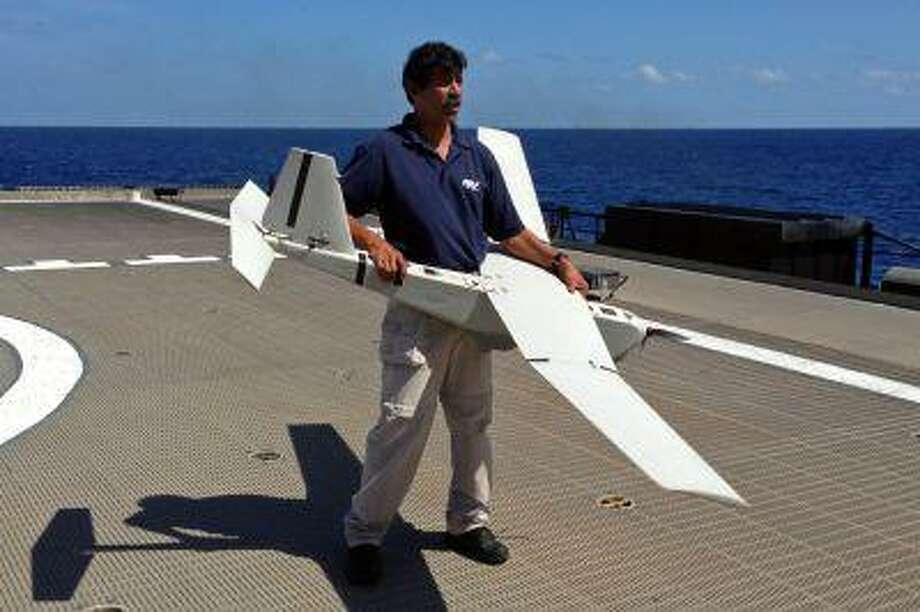 Stuart Orozco, flight operator with Aeronvironment Inc., prepares lo launch a UAS (unmanned aircraft system) named Puma from the deck of the U.S. Navy high speed vessel Swift near Key West, Florida, Friday, April 26, 2013. The U.S. Navy on Friday began testing two new aerial tools, borrowed from the battlefields of Afghanistan and Iraq, that officials say will make it easier to detect, track and videotape drug smugglers in action. (AP Photo/Ben Fox) Photo: ASSOCIATED PRESS / AP2013