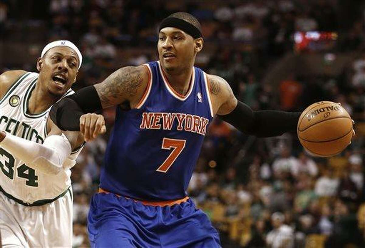 New York Knicks' Carmelo Anthony (7) holds off Boston Celtics' Paul Pierce during the fourth quarter of New York's 90-76 win in Game 3 of a first-round NBA basketball playoff series in Boston, Friday, April 26, 2013. (AP Photo/Winslow Townson)