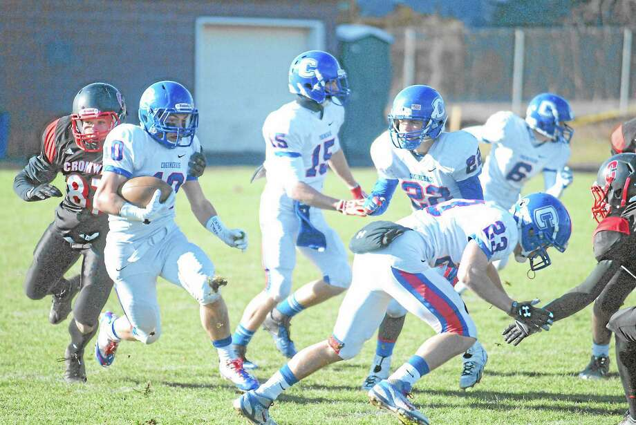 Coginchaug senior Jack Granger (10) tries to break through the grasp of Cromwell freshman linebacker Kyle Theobald (87). Granger led all rushers with 101 yards in the Blue Devils 35-6 victory Thursday at Pierson Park. Photo: Jimmy Zanor — Middletown Press