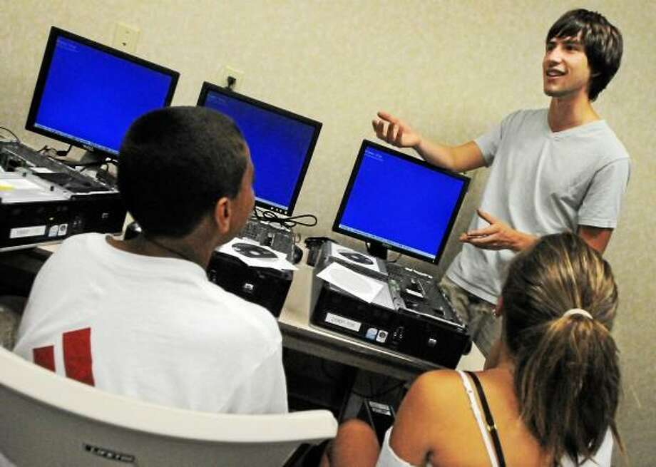 Catherine Avalone - The Middletown Press Davon Colon and Eve Vasso listen to instructor Andrew Brothers, 22 a member of the Middlesex Community College Computer Club teach a computer class at Joy Camp at Shiloh Christian Church at 693 Saybrook Road in Middletown Wednesday afternoon. / TheMiddletownPress
