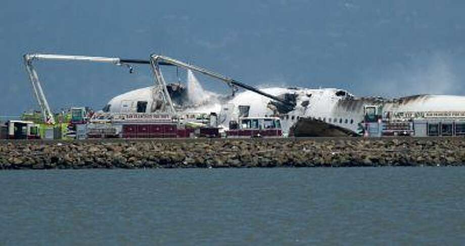 A fire truck sprays water on Asiana Flight 214 after it crashed at San Francisco International Airport on Saturday, July 6, 2013, in San Francisco. Photo: ASSOCIATED PRESS / AP2013