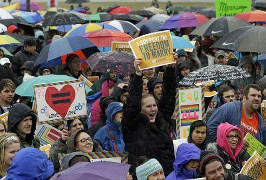 "Hundreds turned out to brave rain, ice pellets and snow during a rally in support of a bill to legalize gay marriage at the Minnesota State Capitol, Thursday, April 18, 2013 in St. Paul, Minn. Gov. Mark Dayton told the crowd he hoped legislators pass gay marriage this year. He says people have ""a constitutional right and an American right to marry who you love."" Bills to legalize gay marriage passed House and Senate committees last month. They could get full House and Senate votes in the next few weeks, but it's not yet clear if backers have enough support to pass it. (AP Photo/Jim Mone) Photo: AP / AP"