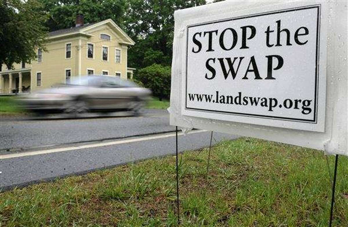 A sign protesting a land swap is seen in Haddam, Conn., Thursday, May 19, 2011. A proposal to swap state-owned open space for land adjacent to a state forest is drawing praise for its potential to bring tourism to Haddam. But critics say state conservation land should not be used for private development. (AP Photo/Jessica Hill)
