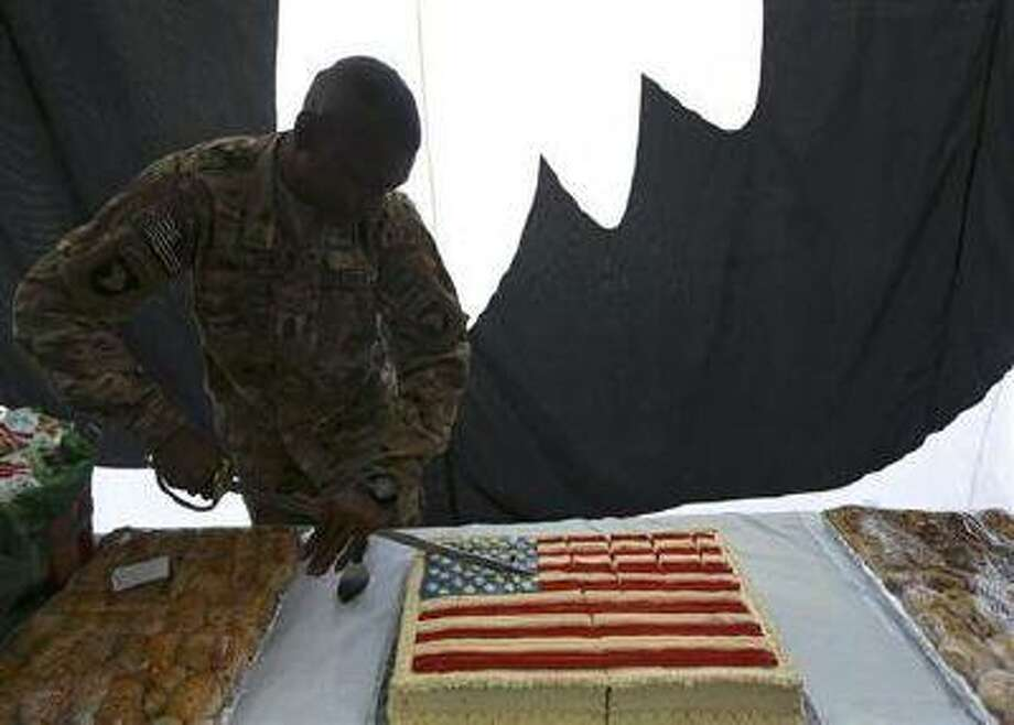 A U.S. soldier cuts into a cake during Fourth of July celebrations at the Bagram airbase, north of Kabul July 4.