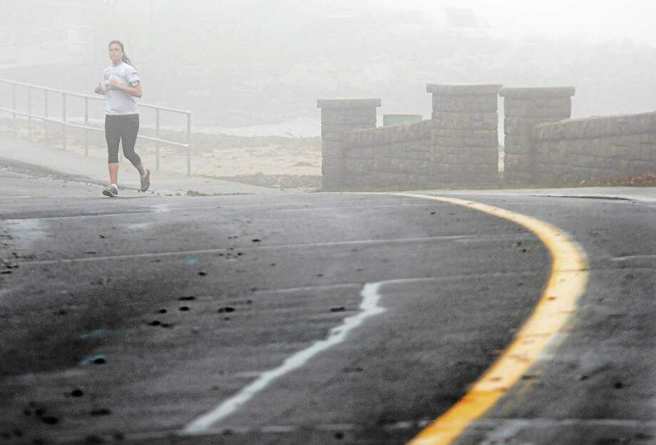 Ashley Sadowski of Branford jogs at Branford Point in the fog, drizzle, and balmy temperature early Wednesday morning in Branford. Photo: Peter Hvizdak — New Haven Register  / ©Peter Hvizdak /  New Haven Register