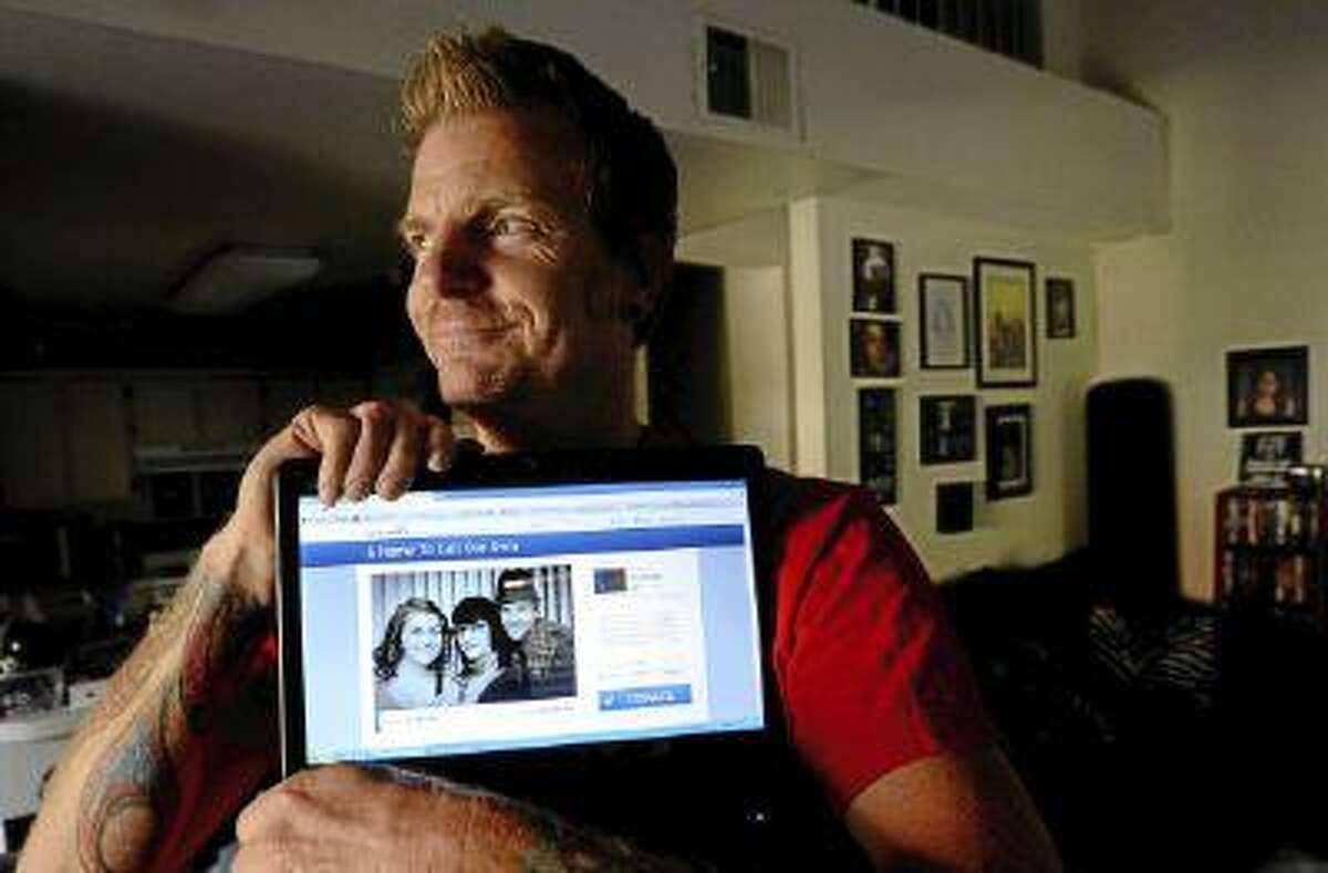Chris Payne poses with his gofundme.com crowdfunding page.