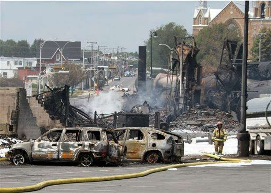This photo provided by Surete du Quebec, shows wrecked oil tankers and debris from a runaway train on Monday, July 8, 2013 in Lac-Megantic, Quebec, Canada.  A runaway train derailed igniting tanker cars carrying crude oil early Saturday, July 6.  At least thirteen people were confirmed dead and nearly 40 others were still missing in a catastrophe that raised questions about the safety of transporting oil by rail instead of pipeline.  (AP Photo/Surete du Quebec, The Canadian Press) Photo: AP / Surete du Quebec via The Canadian Press