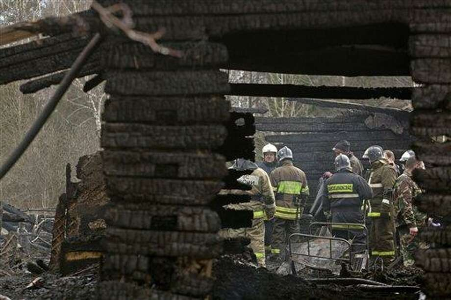 Ministry for Emergency Situations workers and fire fighters work at the site of a fire at a psychiatric hospital Friday morning, April 26, 2013. A fire raged through a psychiatric hospital outside Moscow early Friday, killing 38 people, including two nurses, emergency officials said. Police said the fire, which broke out at about 2 a.m. local time (7 p.m. Eastern, 2300 GMT) in the one-story hospital in the Ramenskoye settlement, was caused by a short circuit. (AP Photo/Pavel Sergeyev) Photo: ASSOCIATED PRESS / AP2013