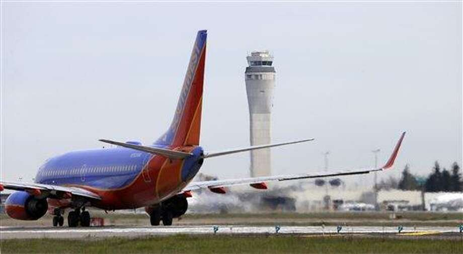 This photo taken April 23, 2013 shows a Southwest airlines jet waiting to depart in view of the air traffic control tower at Seattle-Tacoma International Airport in Seattle. With disgruntled passengers complaining about airline flight delays, Republican lawmakers and the airline industry pounced on the Obama administration. The glitch was invented by the White House for political reasons, they charged, and officials waited until the last minute to warn Congress and the airlines of the impending upheaval. (AP Photo/Elaine Thompson) Photo: AP / AP
