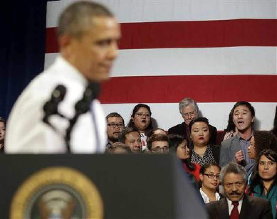 President Barack Obama stops his speech and turns around in response to an unidentified man, right, who heckled him about anti-deportation policies during a speech in San Francisco. Photo: AP / AP