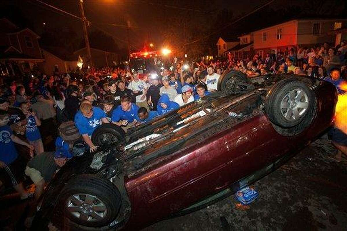 Kentucky fans flip a car on State Street as they celebrate Kentucky's 69-61 win over Louisville in an NCAA Final Four semifinal college basketball tournament game Saturday in Lexington, Ky. Associated Press