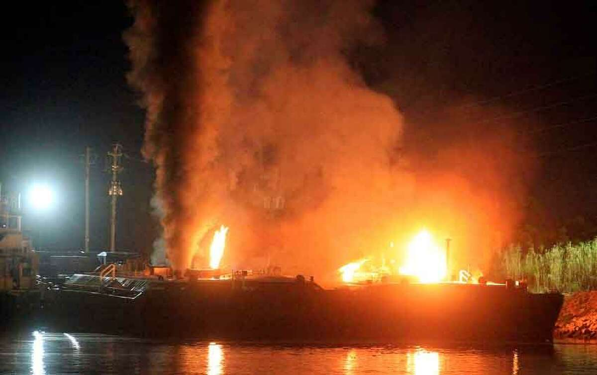 Fire burns aboard two fuel barges along Mobile River after explosions sent three workers to the hospital Wednesday April 24, 2013. Fire officials have pulled units back from fighting the fire due to the explosions and no immediate threat to lives. (AP Photo/Press Register, Glenn Baeske)