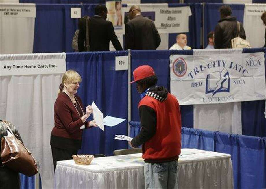 In this Thursday, April 11, 2013, photo, Kathie Maiello of Any-Time Home Care, left, talks with Jashod Chaney of Albany at the Dr. King Career Fair at the Empire State Plaza Convention Center, in Albany, N.Y.  The Labor Department reports on the number of Americans who applied for unemployment benefits last week on Thursday, April 25, 2013. (AP Photo/Mike Groll) Photo: AP / AP