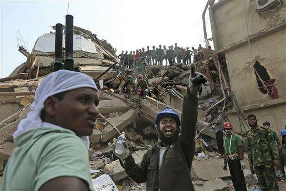 A Bangladeshi rescuer shouts for assistance as another waits with a stretcher fro injured or dead at the site of a building that collapsed Wednesday in Savar, near Dhaka, Bangladesh, Thursday, April 25, 2013. By Thursday, the death toll reached at least 194 people as rescuers continued to search for injured and missing, after a huge section of an eight-story building that housed several garment factories splintered into a pile of concrete. (AP Photo/Kevin Frayer) Photo: AP / AP
