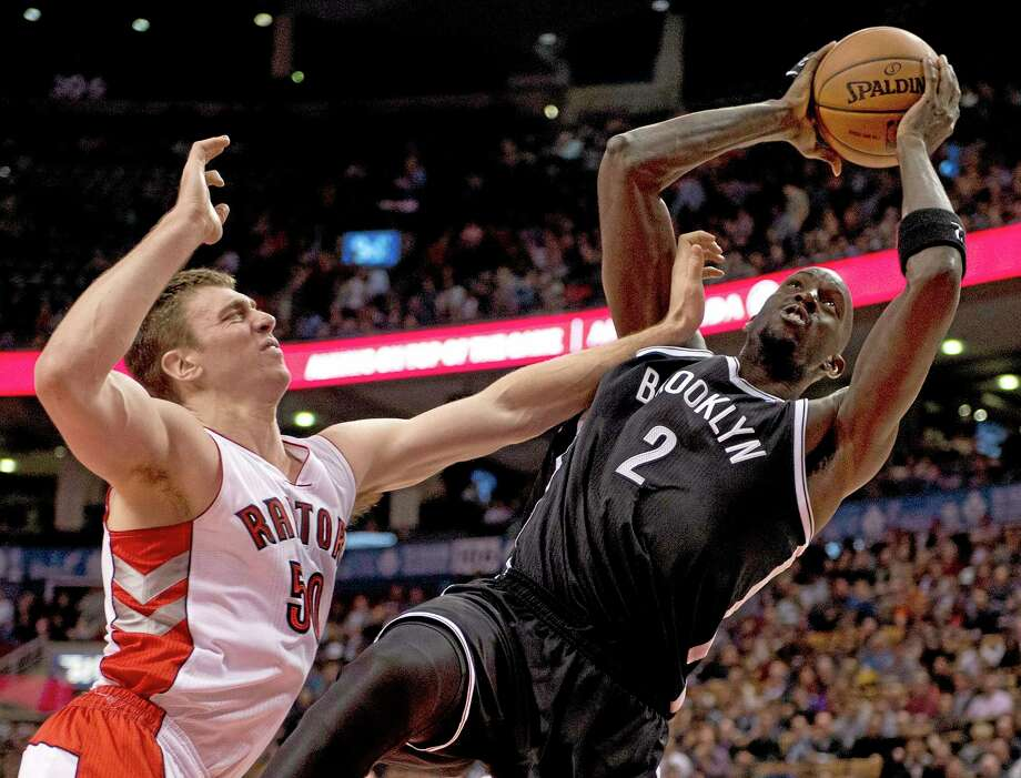 Brooklyn Nets forward Kevin Garnett (2) tries to shoot under heavy pressure from Toronto Raptors forward Tyler Hansbrough, left, during the second half of Tuesday's game in Toronto. Photo: Frank Gunn — The Canadian Press  / cp