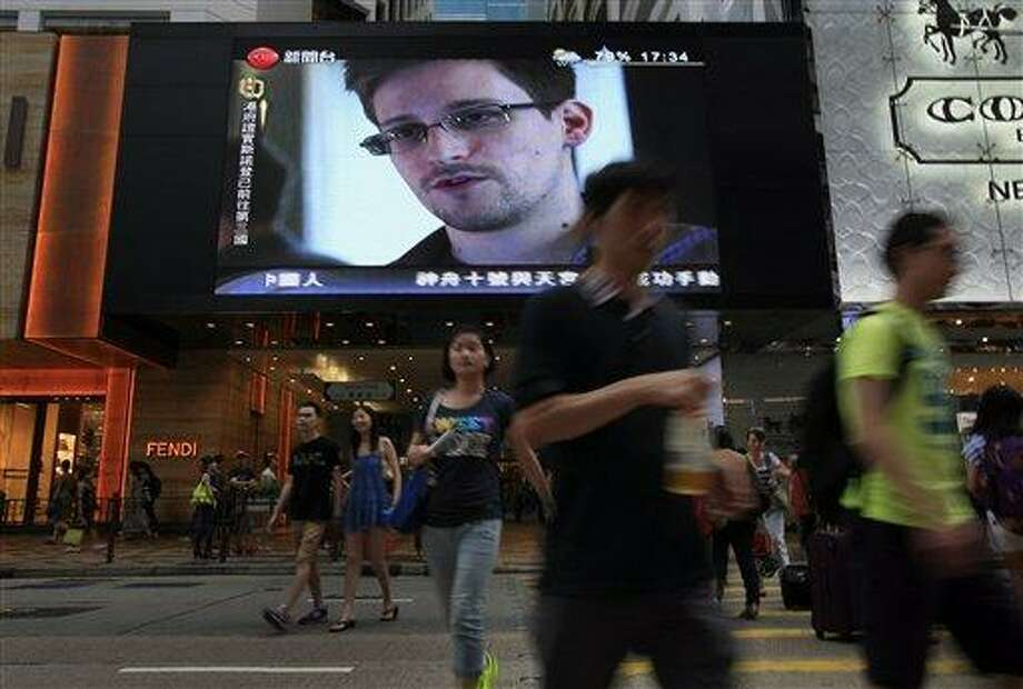 FILE - This June 23, 2013 file photo shows a TV screen shows a news report of Edward Snowden, a former CIA employee who leaked top-secret documents about sweeping U.S. surveillance programs, at a shopping mall in Hong Kong. President Barack Obama brushed aside sharp European criticism on Monday, suggesting all nations spy on each other, as the French and Germans expressed outrage over alleged U.S. eavesdropping on European Union diplomats. American analyst-turned-leaker Edward Snowden, believed to be stranded for the past week at Moscow's international airport, applied for political asylum to remain in Russia. (AP Photo/Vincent Yu, File) Photo: AP / AP