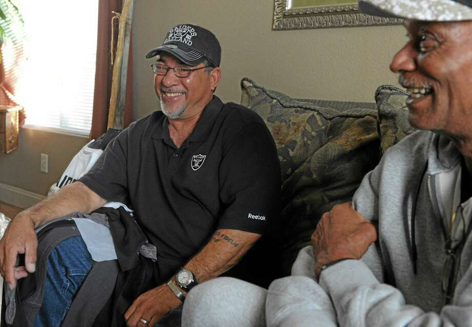 Stockton resident Donnie Navidad, 61, left, laughs with former Oakland Raider Willie Brown, Monday, Nov. 25, 2013, in Stockton, Calif., as he talks about saving a young woman's life after a Raiders NFL football game at the Coliseum. Navidad said when he saw a woman jumping from the upper deck at the Oakland Raiders' stadium on Sunday, his military instincts immediately kicked in as he lunged forward trying to catch her. (AP Photo/The Record, Calixtro Romias) Photo: AP / © Record Newspaper  2012