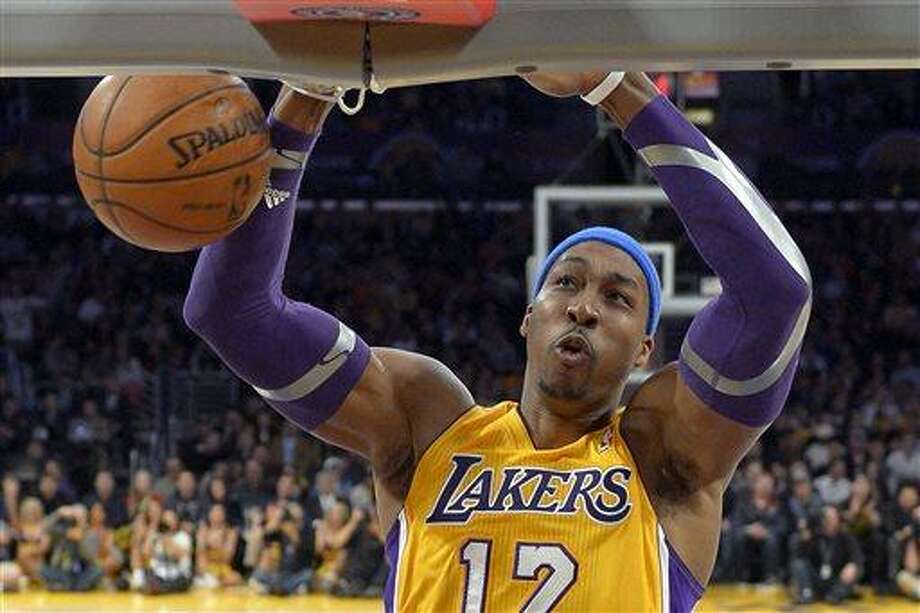 """FILE - In this Jan. 25, 2013, file photo, Los Angeles Lakers center Dwight Howard dunks during the first half of their NBA basketball game against the Utah Jazz, in Los Angeles. Dallas Mavericks owner Mark Cuban tweeted Friday, July 5, 2013, that it was """"time to get back to work"""" amid multiple media reports that Dallas was out of the running for free agent Howard. (AP Photo/Mark J. Terrill, File) Photo: AP / AP"""