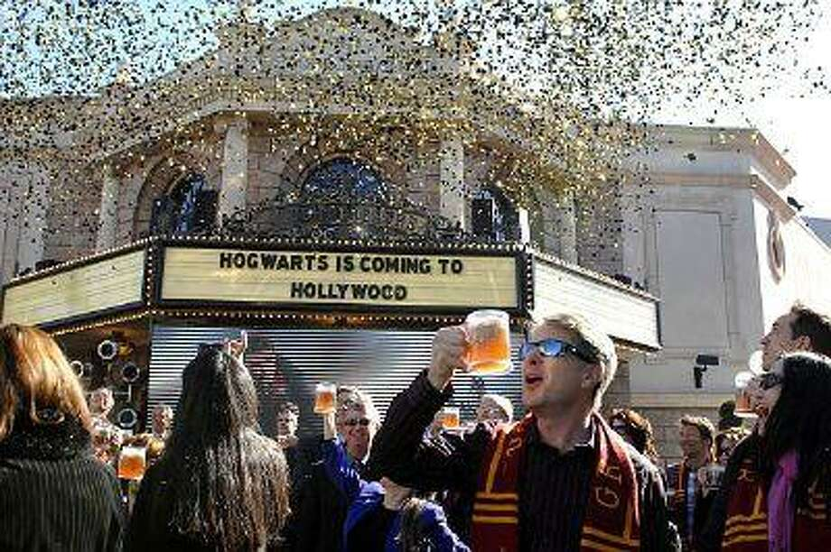 People hold butterbeer as confetti flutters down during the announcement of plans to build the Wizarding World of Harry Potter at Universal Studios Hollywood, Tuesday, December 6, 2011. (Michael Owen Baker/Staff Photographer)