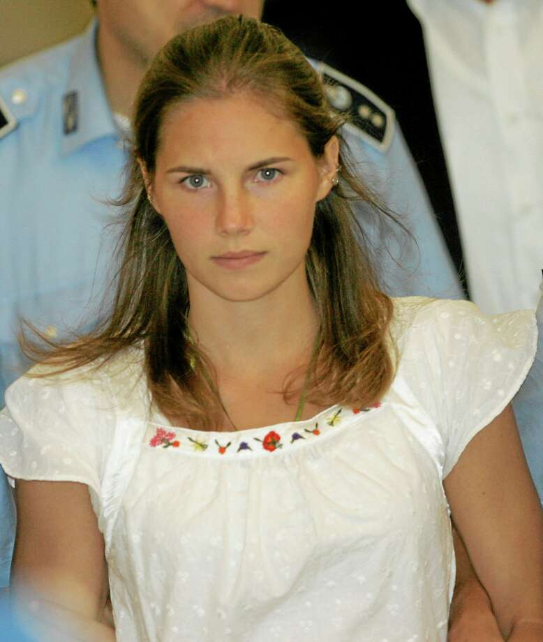 FILE - In this Tuesday Sept. 16, 2008 file photo, Amanda Knox is escorted by Italian penitentiary police officers from Perugia's court after a hearing, central Italy. An Italian prosecutor on Tuesday, Nov. 26, 2013 demanded that an appellate court find Amanda Knox guilty of the 2007 murder of her British roommate and sentence her to 26 years for the killing. Prosecutor Alessandro Crini made the demand after more than 10 hours of closing arguments over two days during which he argued that Knox and her co-defendant Raffaele Sollecito acted in concert with a third man, who was convicted separately, in an explosion of violence sparked by tensions between the roommates over cleanliness. (AP Photo/Antonio Calanni, File) Photo: AP / AP