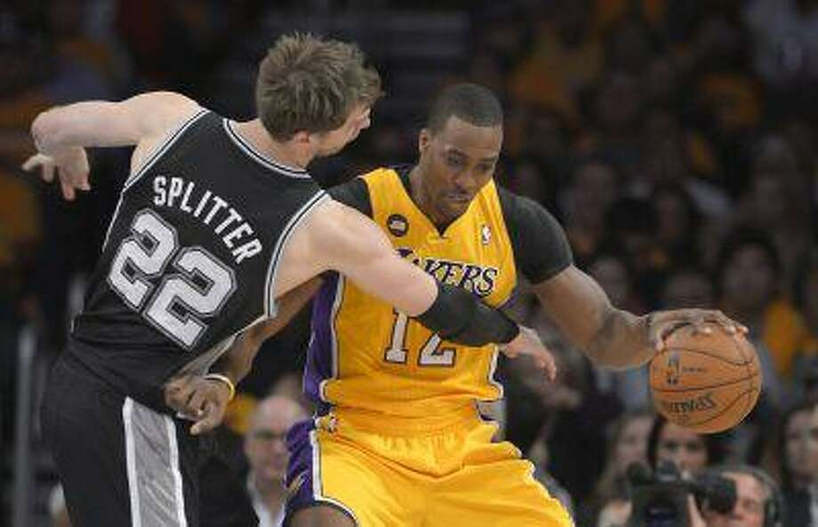 Los Angeles Lakers center Dwight Howard, right, drives around San Antonio Spurs center Tiago Splitter, of Brazil, during the first half in Game 3 of a first-round NBA basketball playoff series, Friday, April 26, 2013, in Los Angeles. Photo: ASSOCIATED PRESS / MARK J. TERRILL2013