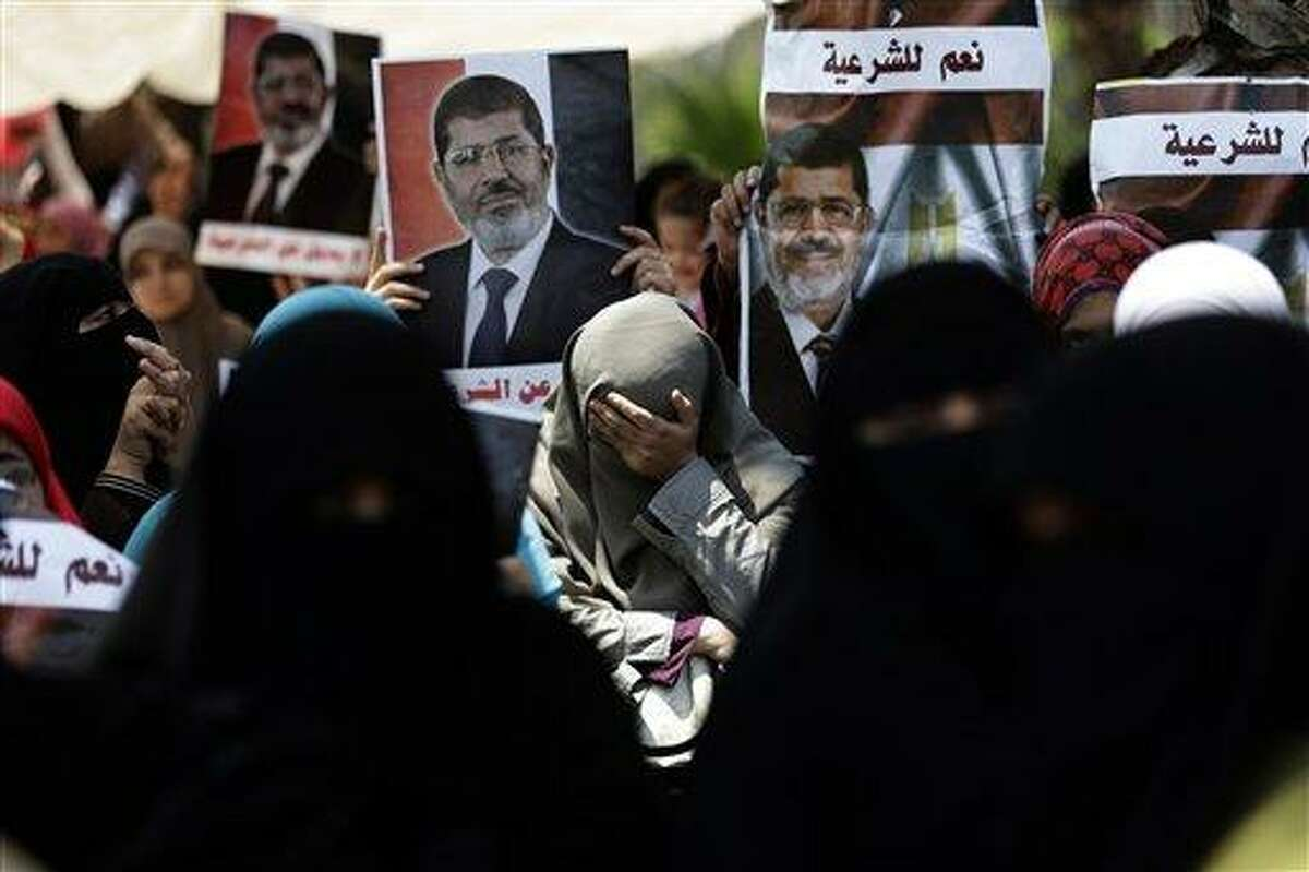 A supporter of ousted Egypt's President Mohammed Morsi cries during a protest near the University of Cairo, Giza, Egypt, Friday, July 5, 2013. Arabic reads,