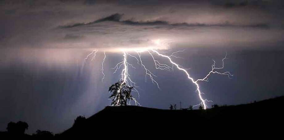 Lightning strikes above the Geysers area of northern Sonoma County, early Thursday, July 4, 2013 near Geyserville Calif.  (AP Photo/Santa Rosa Press Democrat, Kent Porter) Photo: ASSOCIATED PRESS / THE ASSOCIATED PRESS2013