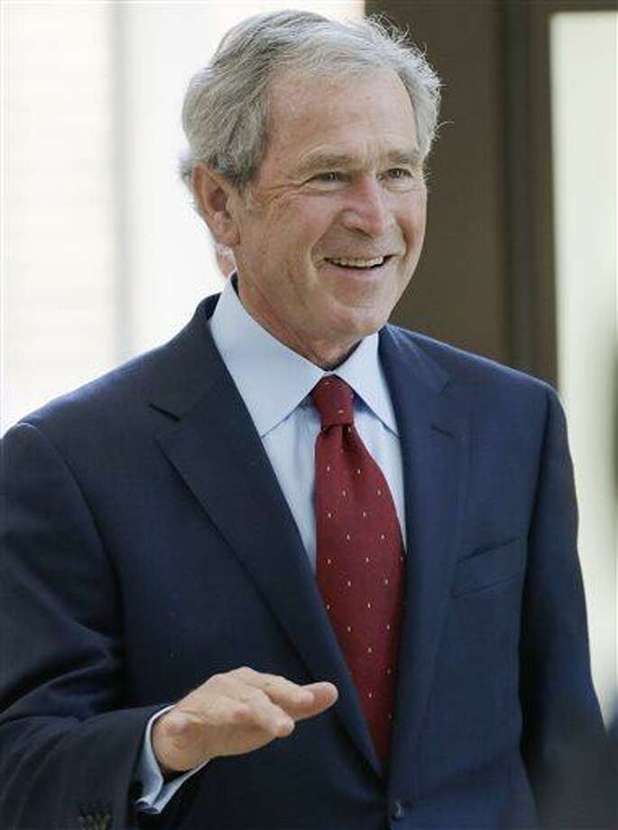 Former President George W. Bush arrives at the signing ceremony for the joint use agreement between the National Archive and the George W. Bush Presidential Center Wednesday, April 24, 2013, in Dallas. Bush and his wife, Laura, attended Wednesday's ceremony in Dallas the day before the official dedication of the George W. Bush Presidential Center. The George W. Bush Foundation raised the money to build the center. The foundation donated the library and museum portion of the center to the National Archives, which provides access to presidential records, documents, historical materials and artifacts over time. (AP Photo/David J. Phillip) Photo: AP / AP