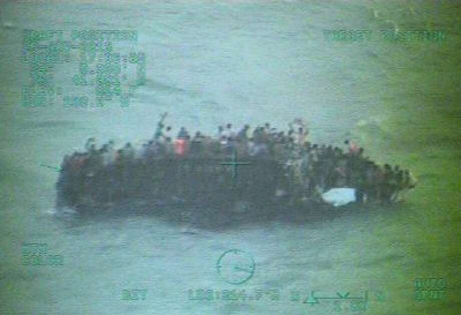 This image taken from video made available by the U.S. Coast Guard shows a group of Haitian migrants sitting on the hull of a capsized sailboat near Staniel Cay, Bahamas on Nov. 26, 2013.