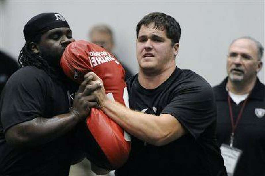Texas A&M's Luke Joeckel, right, works a drill for NFL scouts, March 8, 2013 in College Station, Texas. Photo: AP / AP