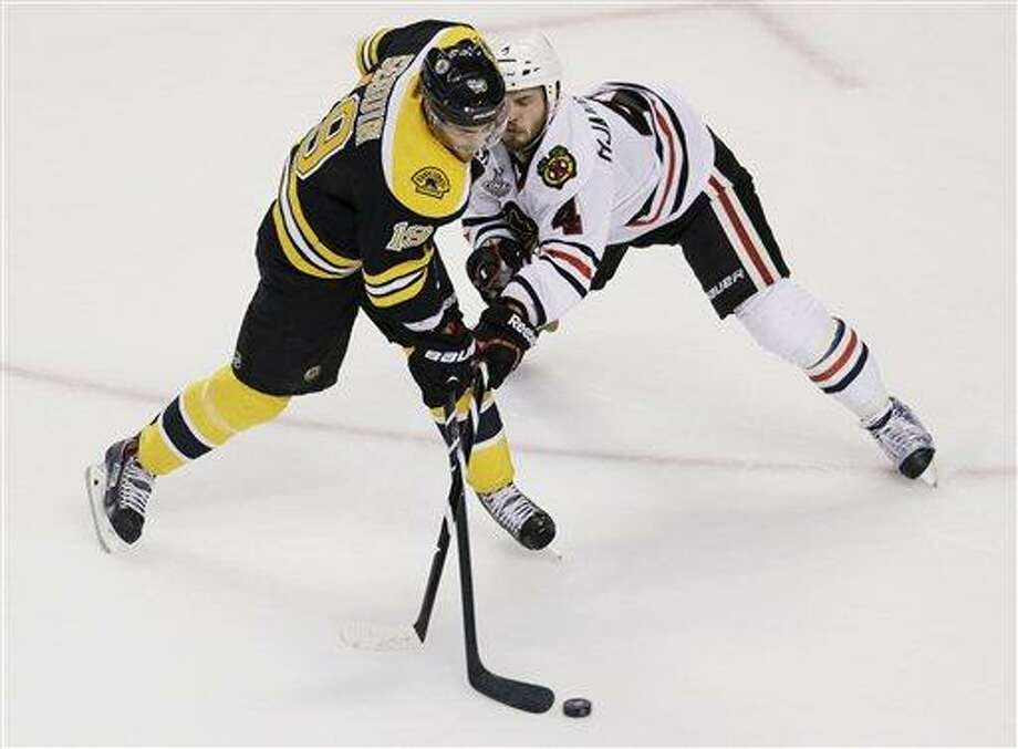 Chicago Blackhawks defenseman Niklas Hjalmarsson (4), of Sweden, checks Boston Bruins center Tyler Seguin (19) during the first period in Game 4 of the NHL hockey Stanley Cup Finals, Wednesday, June 19, 2013, in Boston. (AP Photo/Charles Krupa) Photo: AP / AP