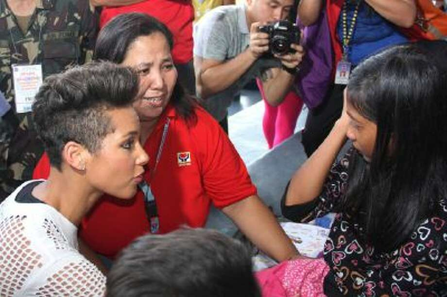 In this photo released by the Philippine Air Force, Grammy-winning singer Alicia Keys, left, talks to a typhoon survivor as she visits the Villamor Air Base in suburban Pasay, south of Manila, Philippines, Monday Nov. 25, 2013. Keys visited the air force base to bring cheer to hundreds of evacuees from eastern Philippine provinces wracked by Typhoon Haiyan earlier this month.