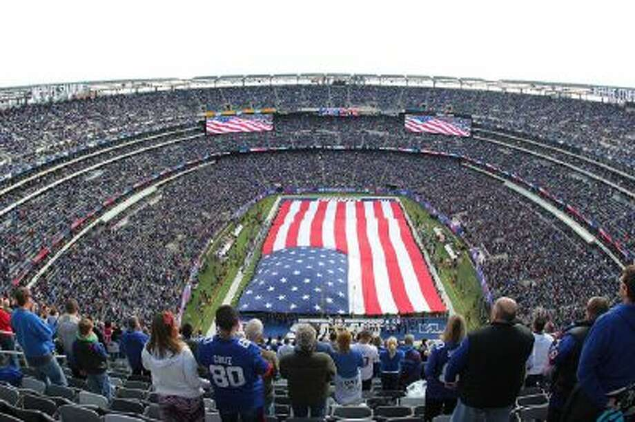 A United States flag covers the field at MetLife Stadium as the New York Giants observe the NFL's Salute to Service before a football game between the Giants and the Oakland Raiders, Sunday, Nov. 10, 2013, in East Rutherford, N.J. The stadium will host the 2014 Superbowl.