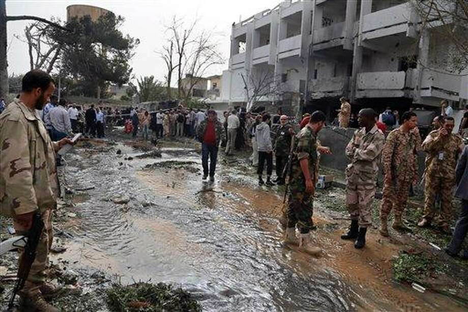 Security personnel inspect the site of a car bomb that targeted the French embassy wounding two French guards and causing extensive material damage in Tripoli, Libya, Tuesday, April 23, 2013. An explosives-laden car was detonated just outside the embassy building in Tripoli's upscale al-Andalus neighborhood, officials said. (AP Photo/Abdul Majeed Forjani) Photo: ASSOCIATED PRESS / AP2013