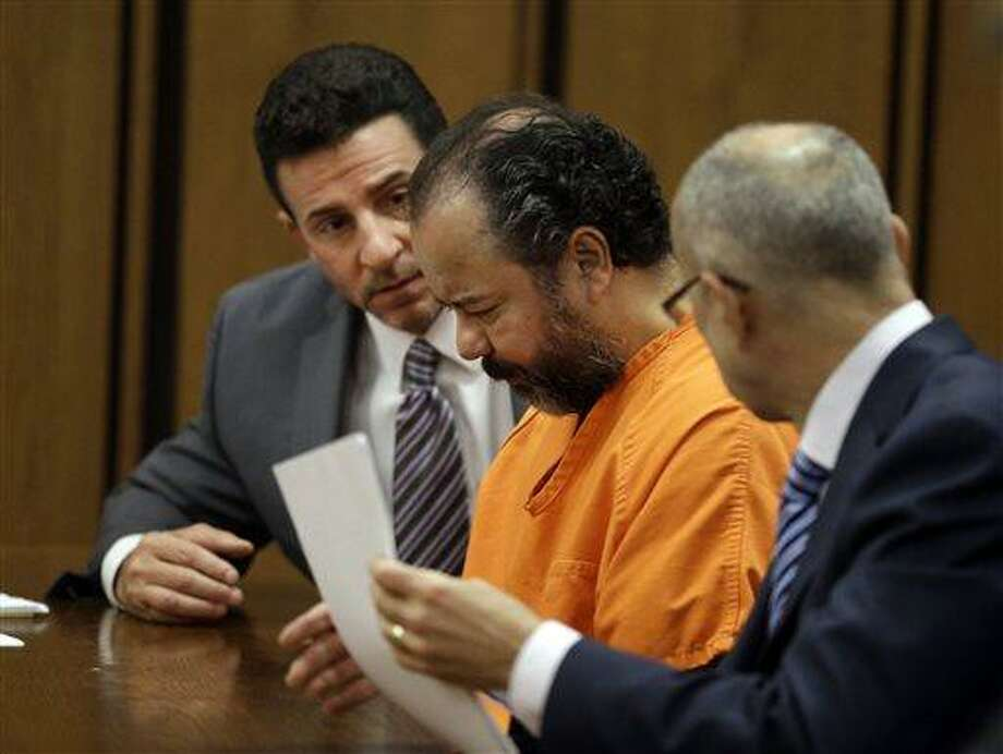 Ariel Castro, center, confers with his attorneys Craig Weintraub, left, and Jaye Schlachet during a pretrial hearing in Cuyahoga County Common Pleas Court in Cleveland, Wednesday, July 3, 2013. Castro is accused of holding three women captive for nearly a decade. (AP Photo/Mark Duncan) Photo: AP / AP