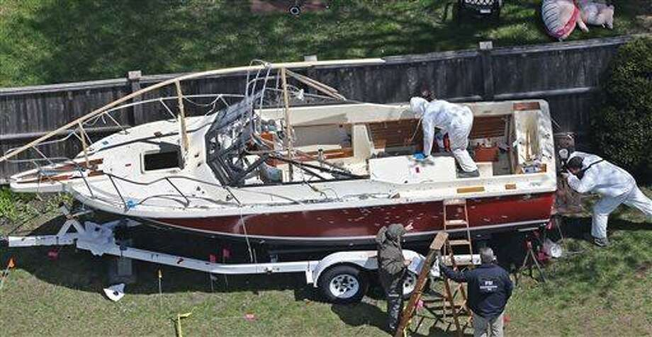 Investigators from the FBI inspect the boat where Boston Marathon bombing suspect Dzhokhar Tsarnaev was found hiding on Friday night in a backyard in Watertown, Mass., Tuesday, April 23, 2013. There is blood spattered on the wheel fender of the trailer and bullet holes in the hull of the boat. Tsarnaev had gunshot wounds to the head, neck, legs and hands when he was captured hiding out in the boat on Friday night, April 19, 2013. (AP Photo/The Boston Globe, David L. Ryan)  BOSTON HERALD OUT; QUINCY OUT; NO SALES Photo: AP / The Boston Globe