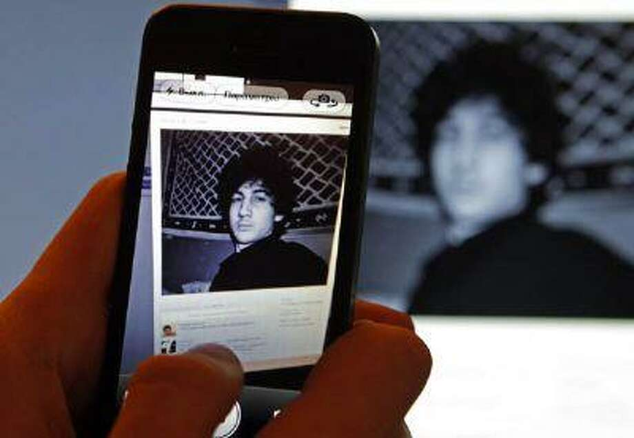 A photograph of Djohar Tsarnaev, who is believed to be Dzhokhar Tsarnaev, a suspect in the Boston Marathon bombing, is seen on his page of Russian social networking site Vkontakte (VK), as pictured on a monitor and a mobile phone in St. Petersburg April 19, 2013. Photo: REUTERS / X90067