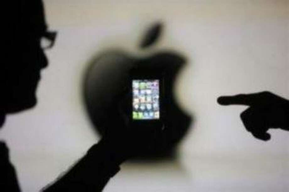 Men are silhouetted against a video screen with an Apple logo as they pose with an Apple iPhone 4 smartphone in this photo illustration taken in the central Bosnian town of Zenica, May 17, 2013.