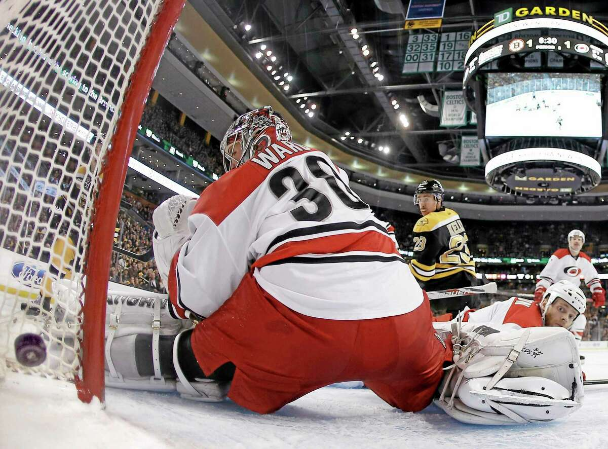 The Bruins' Chris Kelly (23) looks on as Carolina Hurricanes goalie Cam Ward can't stop this second-period goal by Reilly Smith during the Bruins' 3-2 overtime win on Saturday in Boston.