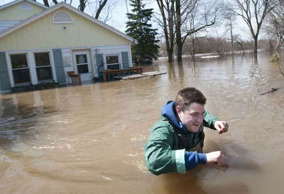 Joe Biggerstaff wades away from his mother's Konkle Drive home on the Grand River north of downtown Grand Rapids, Mich., Sunday, April 21, 2013. The rising Grand River has driven hundreds of people from their homes in several western Michigan communities and was pushing Sunday toward a record high near Grand Rapids. (AP Photo/MLive.com, Chris Clark) Photo: ASSOCIATED PRESS / AP2013