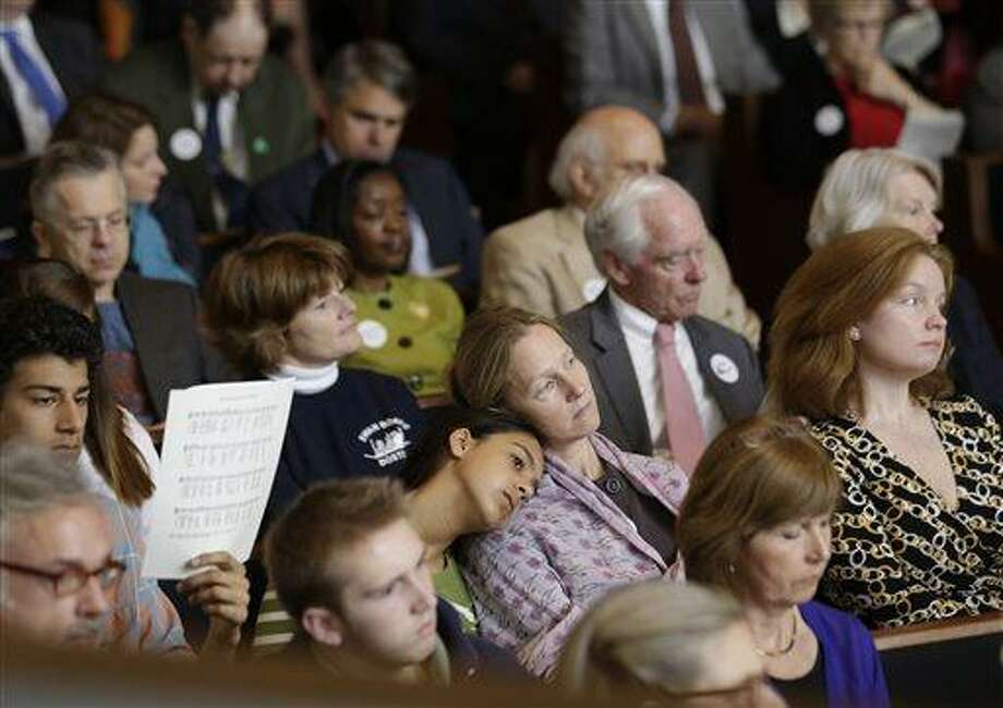 Members of Trinity Episcopal Church in Boston listen to a sermon at Temple Israel, which allowed the Trinity congregation hold Sunday service, Sunday, April 21, 2013, in Boston. Trinity is within the blocked off area near the finish line of the Boston Marathon, where earlier in the week two bombs exploded. (AP Photo/Julio Cortez) Photo: AP / AP