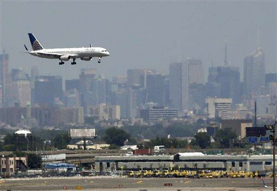 In this July 10, 2012 file photo, a United plane prepares to land at Newark Liberty International Airport in Newark, N.J., with the New York City skyline in the background. Commercial airline flights moved smoothly throughout most of the country on Sunday, April 21, 2013, the first day air traffic controllers were subject to furloughs resulting from government spending cuts, though some delays appeared in the late evening in and around New York. The real test, however, will come Monday, when traffic ramps up. (AP Photo/Julio Cortez, File) Photo: AP / AP