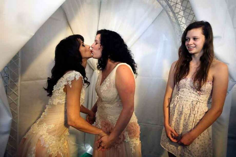 Grace Meier, right, watches her mother Sallee Taylor, center, and partner Andrea Taylor during a wedding ceremony in West Hollywood, Calif., Monday, July 1, 2013. The city of West Hollywood is offering civil marriage ceremonies for same-sex couples free of charge Monday. (AP Photo/Jae C. Hong) Photo: ASSOCIATED PRESS / AP2013
