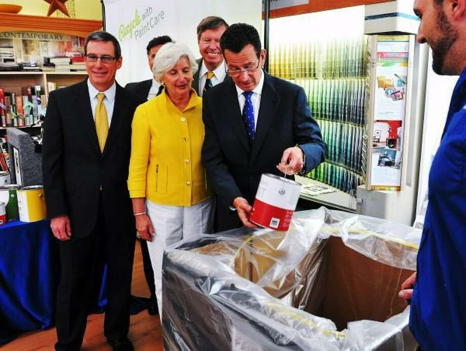Gov. Dannel P. Malloy throws a symbolic can of unused paint away in a receptacle at the Branford Sherwin-Williams paint store. Malloy was in town with other government officials and the DEEP to announce a new program to recycle unused paints. Behind him, left to right is: Andy Dolye, president of the American Coatings Association; DEEP Commissioner Day Esty; Rep. Pat Widlitz and Sen. Ed Meyer. Peter Casolino/Register