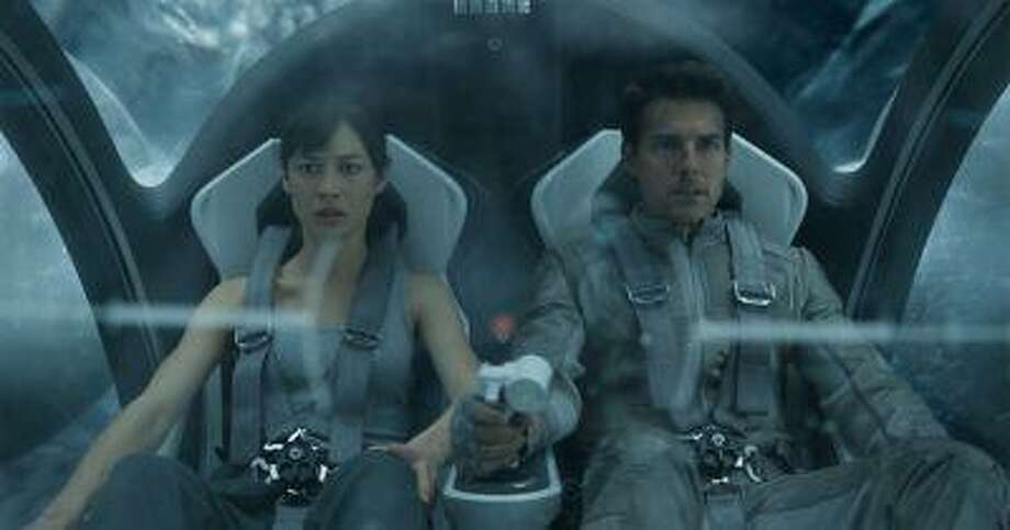"""This film publicity image released by Universal Pictures shows Olga Kurylenko, left, and Tom Cruise in a scene from """"Oblivion."""" (AP Photo/Universal Pictures) Photo: AP / Universal Pictures"""