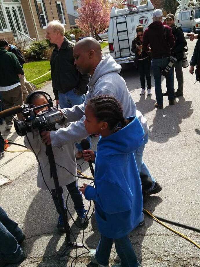On Saturday, Robert Broadway of Roxbury, Mass. brought his daughters Helena, 9, and Haniyah, 10 to the scene where a Boston Marathon suspect was captured less than 24 hours before. He said by letting the girls ask questions and take pictures they can learn more about what happened. Photo by Jenn Smith
