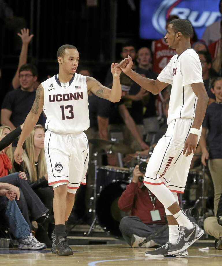 Shabazz Napier, left, DeAndre Daniels and the 18th-ranked Huskies edged Indiana 59-58 on Friday night at Madison Square Garden in New York. Photo: Seth Wenig — The Associated Press  / AP
