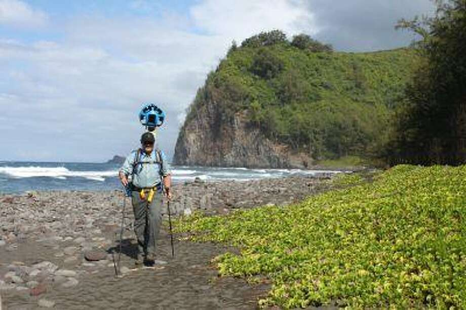 In this undated photo provided by Google, Rob Pacheco, president of Hawaii Forest & Trail, walks across the beach at Pololu Valley near Kapaau, Hawaii, while wearing the Street View Trekker. Hawaii's volcanoes, rainforests and beaches will soon be visible on Google Street View. The Mountain View, Calif., company said Thursday June 27, 2013 it was lending its backpack cameras to a Hawaii trail guide company to capture panoramic images of Big Island hiking trails. (AP Photo/Google) Photo: ASSOCIATED PRESS / AP2013