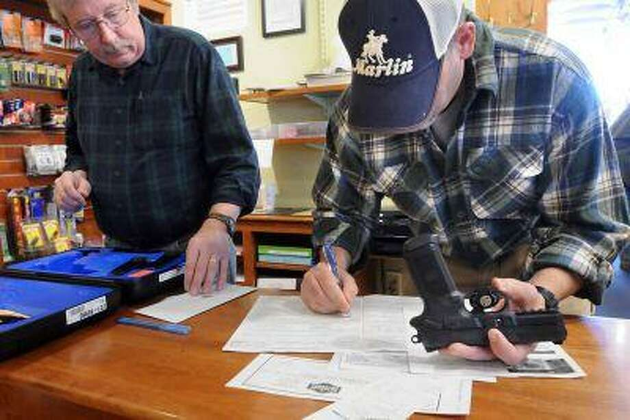 At the TGS Outdoors shop in Branford. Co-owners Brian Owens left and Mike Higgins do the paperwork on the sale of a FNX-45 semi-automatic pistol. Gov. Dan Malloy signed a sweeping gun-control bill into law. (Mara Lavitt/New Haven Register)